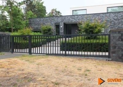 zwart hek met modern huis